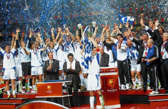 Captain Zagorakis lifts the trophy as the Greeks celebrate their historic feat